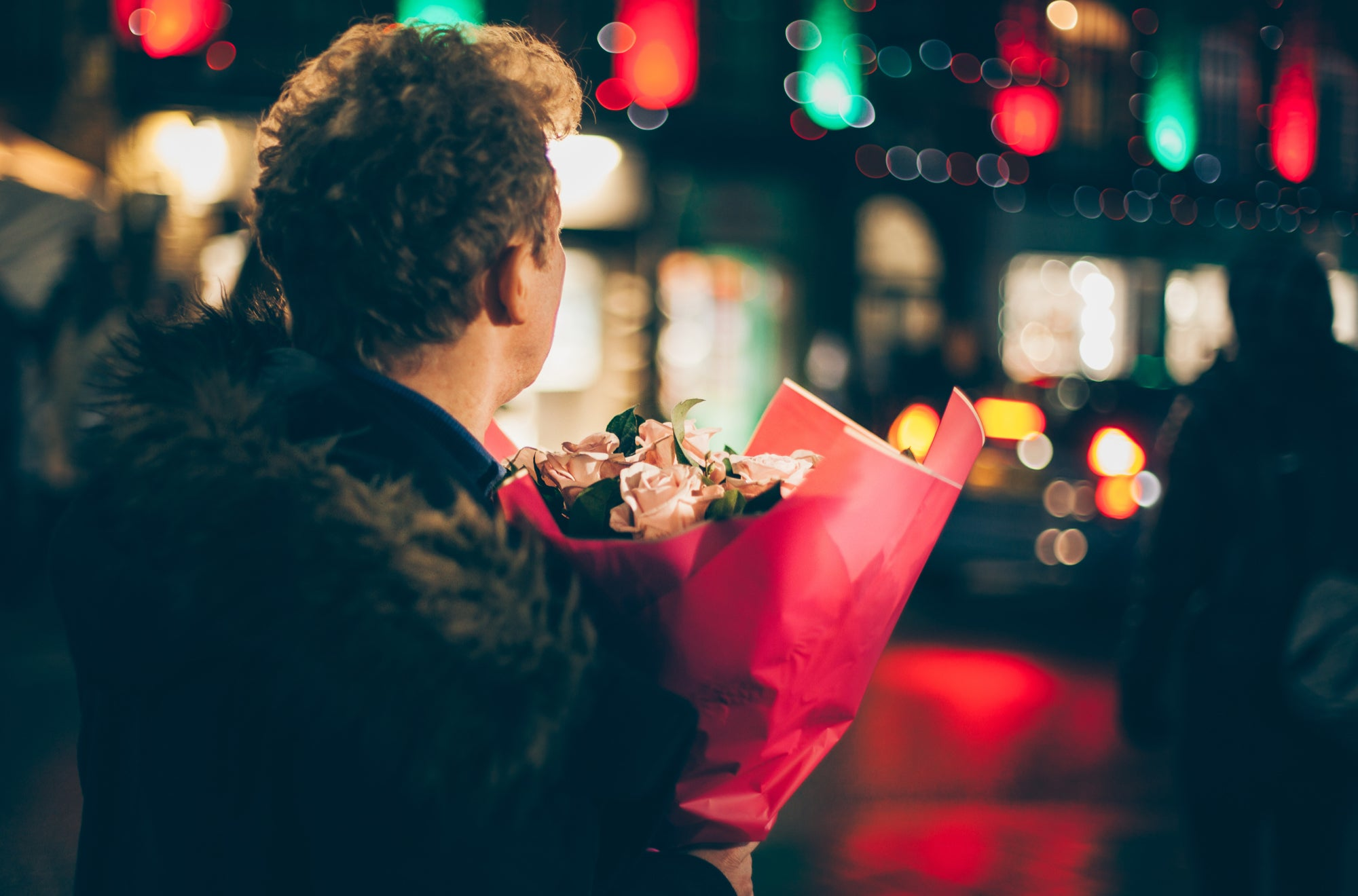 Man in a long-distance relationship wearing a fur coat holds a roses bouquet | Talsam
