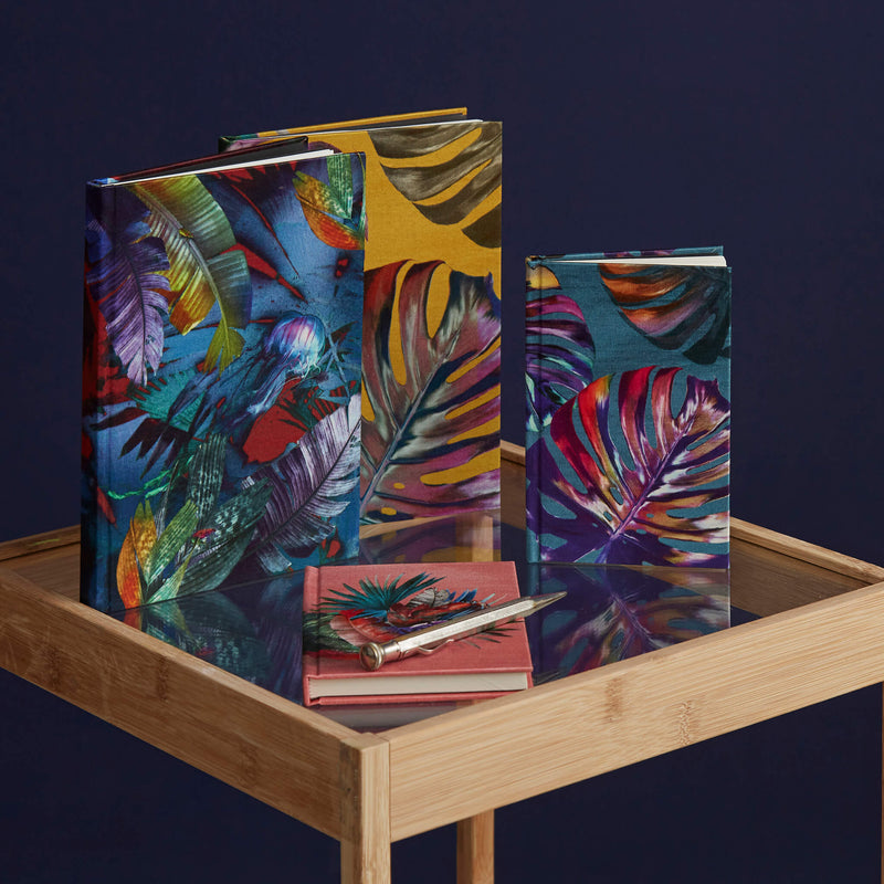 A collection of tropical palm leaf print luxury notebooks by Leila Vibert-Stokes