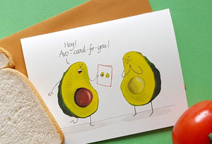 A fun greeting card sitting on it's envelope over a green background. Next to the card sits a piece of bread and a tomato.