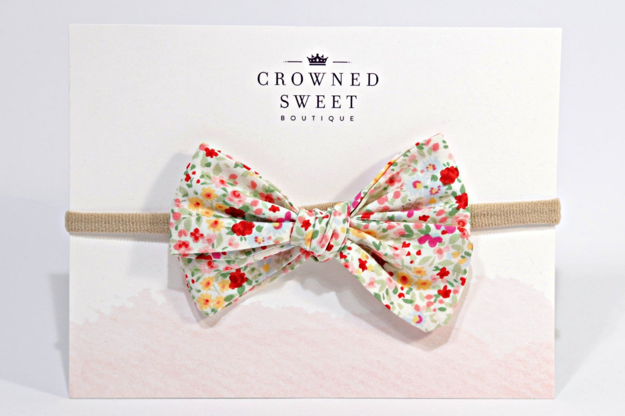 Baby headband with a pink, yellow and green pattern floral bow mounted on its card stock packaging with Crowned Sweet Boutique written top and centre on the cardstock.