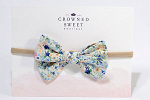 Baby headband with a blue and pink pattern floral bow mounted on its card stock packaging with Crowned Sweet Boutique written top and centre on the cardstock.