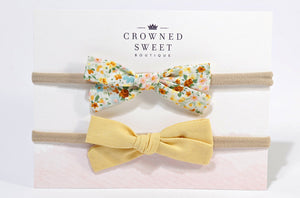 Two baby headbands. The first is with a white bow with pink, red, yellow and green floral pattern and the second is of a soft yellow bow. Both are mounted on its card stock packaging with Crowned Sweet Boutique written top and centre on the cardstock.