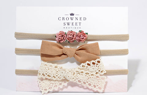 Three baby headbands. The first is three rose buds resting on the band, the second is of a mustard colour bow on the band and the third is of a white lace bow resting on the band. All three are mounted on its card stock packaging with Crowned Sweet Boutique written top and centre on the cardstock.