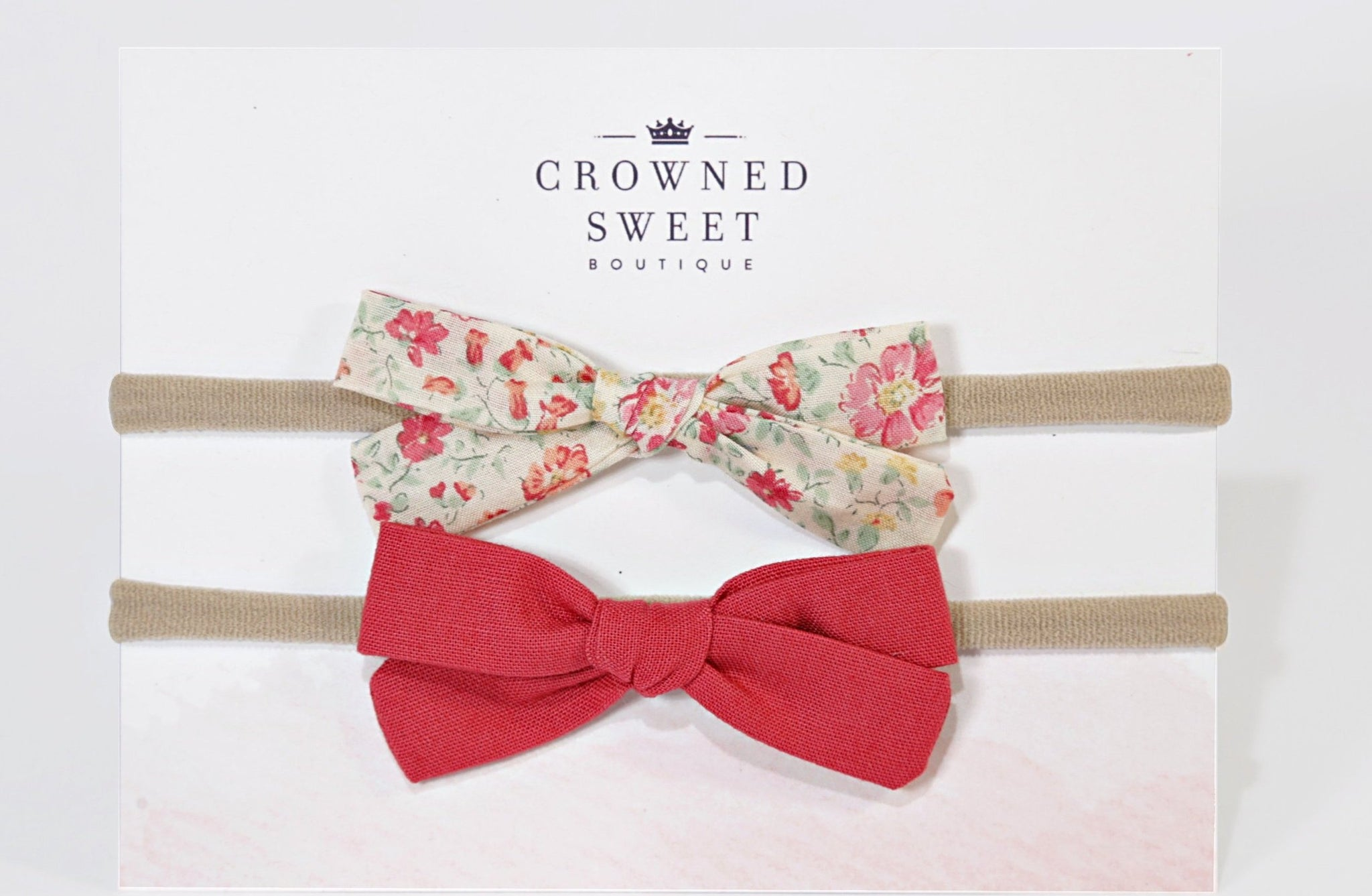Two baby headbands. The first is with a white bow with pink and green floral pattern and the second is of a pink bow. Both are mounted on its card stock packaging with Crowned Sweet Boutique written top and centre on the cardstock.