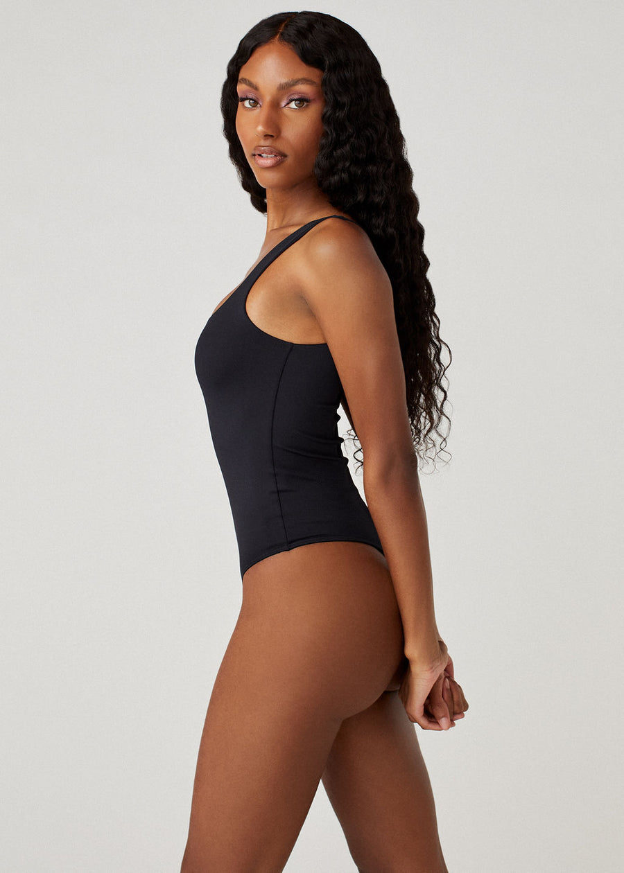 Model in a sideways pose wearing the Sheera bodysuit in black.