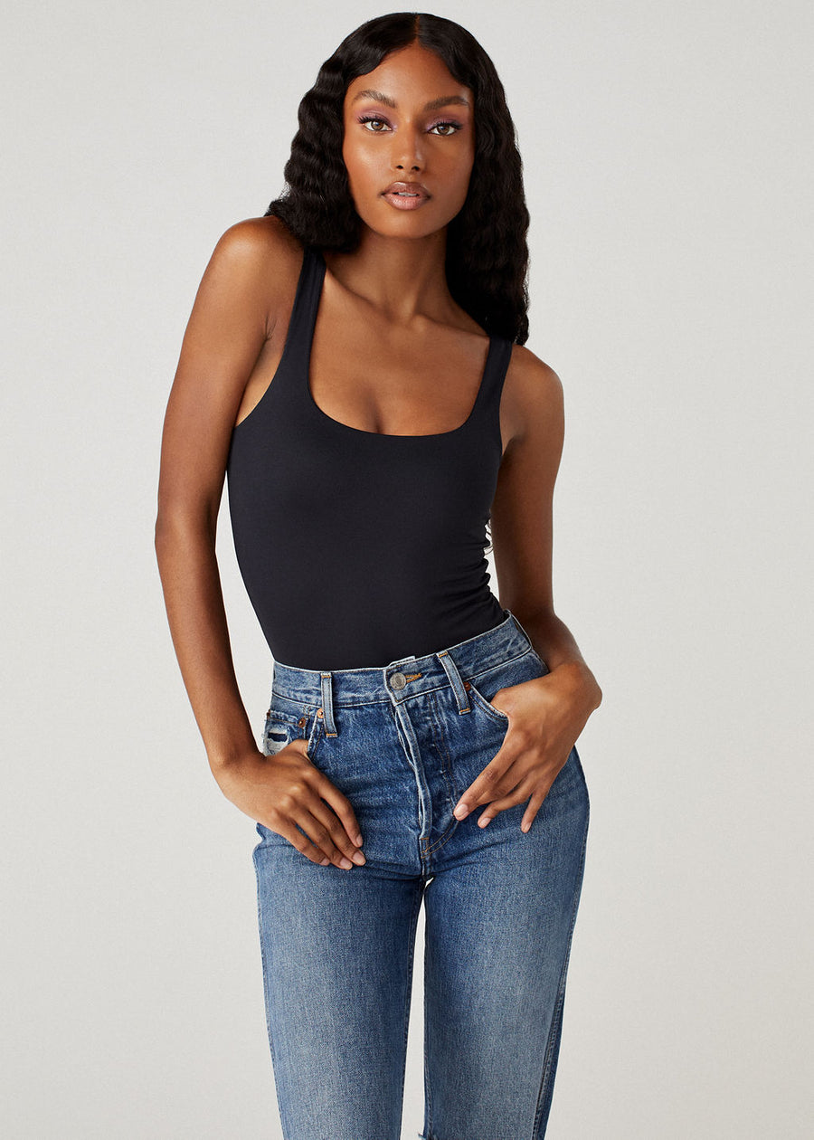 Model wearing slim blue jeans and the Sheera bodysuit in black.