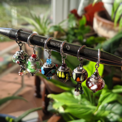 a row of beaded dangles hang from a large knitting needle in front of a background of plants