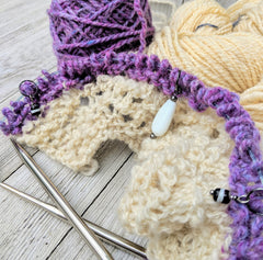 white and purple sample knitting project with three stitch markers illustrating their use to mark the center and inside the decorative edges