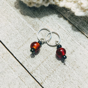 two stitch markers for knitting or crochet with apple red and metallic green glass beads on silver