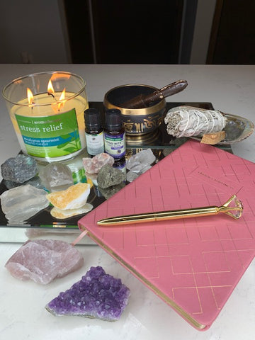 candle, sage, Palo Santo, abalone shell, essential oils, crystals, a journal, a pen and a singing bowl.