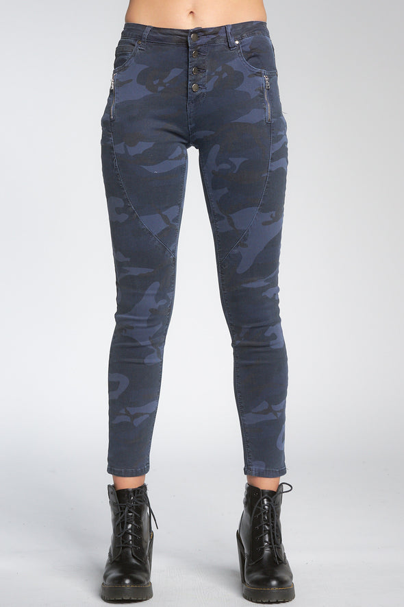 Bottom shot of model facing front wearing navy blue camo-print jeans with buttons, worn with black booties.