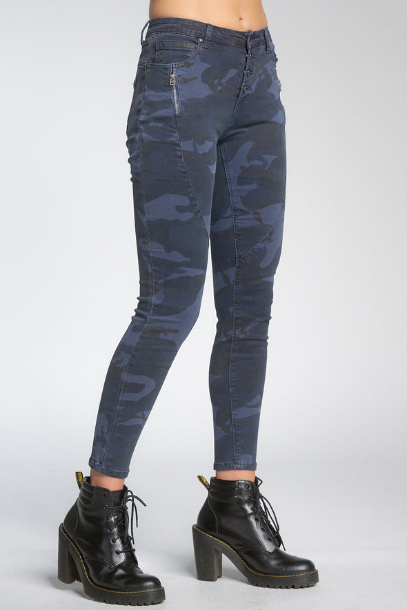 Bottom shot of model facing sideways wearing navy blue camo-print jeans with buttons, worn with black booties.