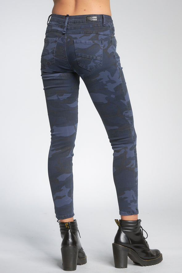 Bottom shot of model facing back wearing navy blue camo-print jeans with buttons, worn with black booties.