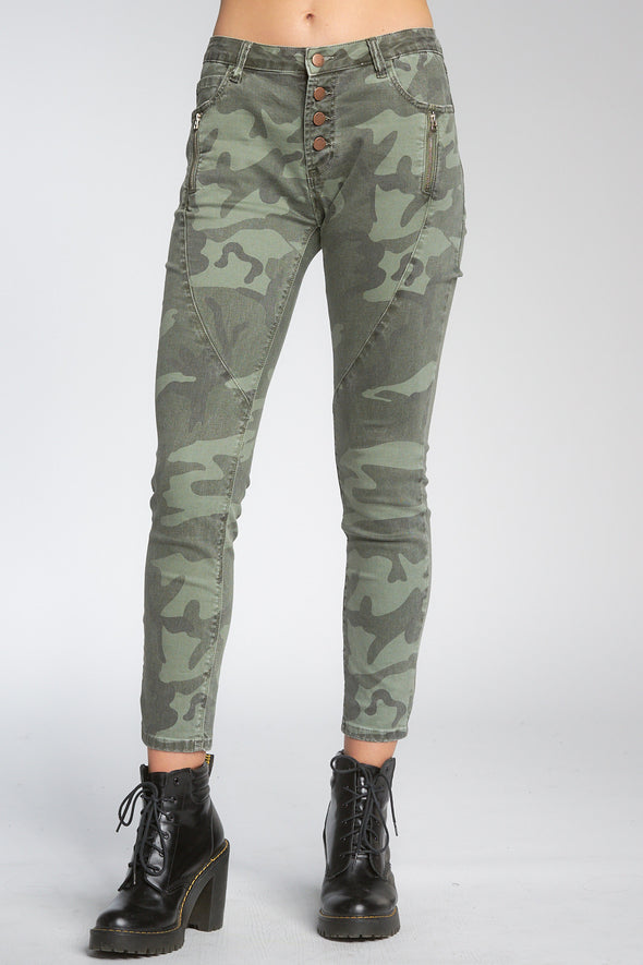 Bottom shot of model facing front wearing green camo-print jeans with buttons, worn with black booties.