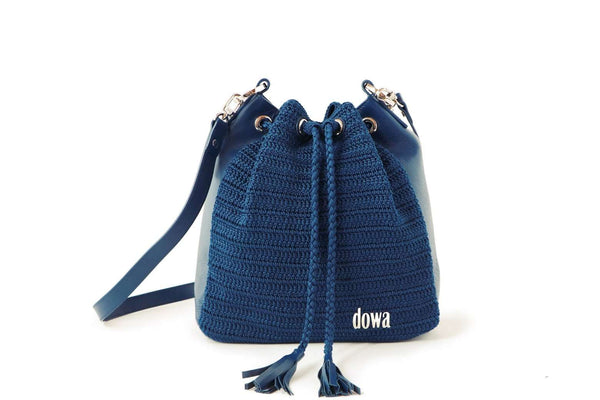 Blue handmade, crochet crossbody ladies handbag with a long red leather strap, two tassels as compartment closure, a dowa metal silver logo, and red leather side body