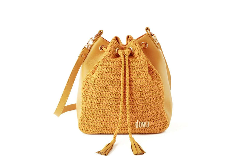 Yellow handmade, crochet crossbody ladies handbag with a long red leather strap, two tassels as compartment closure, a dowa metal silver logo, and red leather side body