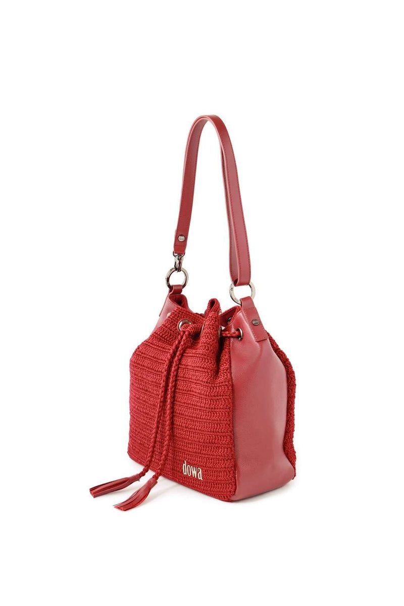 Red handmade, crochet crossbody ladies handbag with a long red leather strap, two tassels as compartment closure, a dowa metal silver logo, and red leather side body