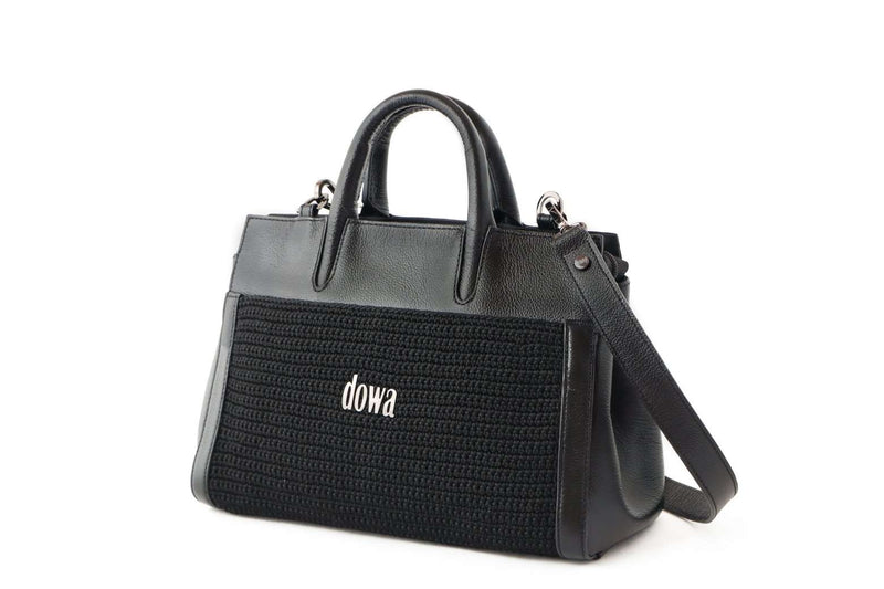 Black hand-crafted ladies handbag, with a detachable shoulder strap and dual top tubular handles. Crochet style on the exterior and a Dowa metal silver logo attached on the centre. Discrete external zip at the top.