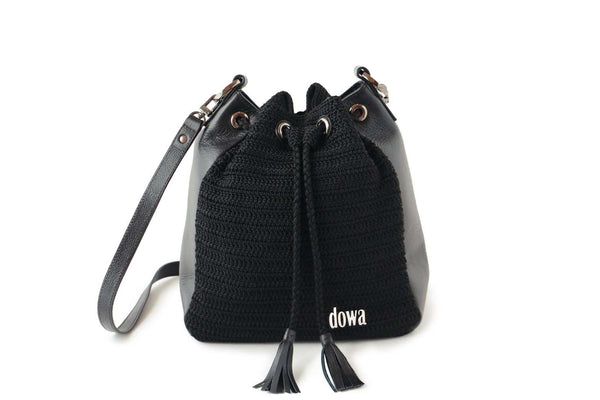Black handmade, crochet crossbody ladies handbag with a long red leather strap, two tassels as compartment closure, a dowa metal silver logo, and red leather side body