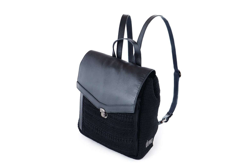 Black crochet backpack with genuine leather flap-over closure. Adjustable leather ribbon straps, with a similar looking carry handle loop. Concealed external zipped compartment. Dowa metal silver logo attached to the side crocheted panel of bag.