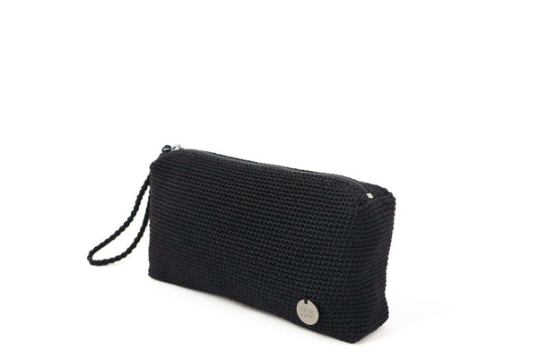 Black crochet rectangular pouch with discrete zip at the top. Small silver metal logo attached to the bottom right hand side. Plaited wrist loop attached to zip.