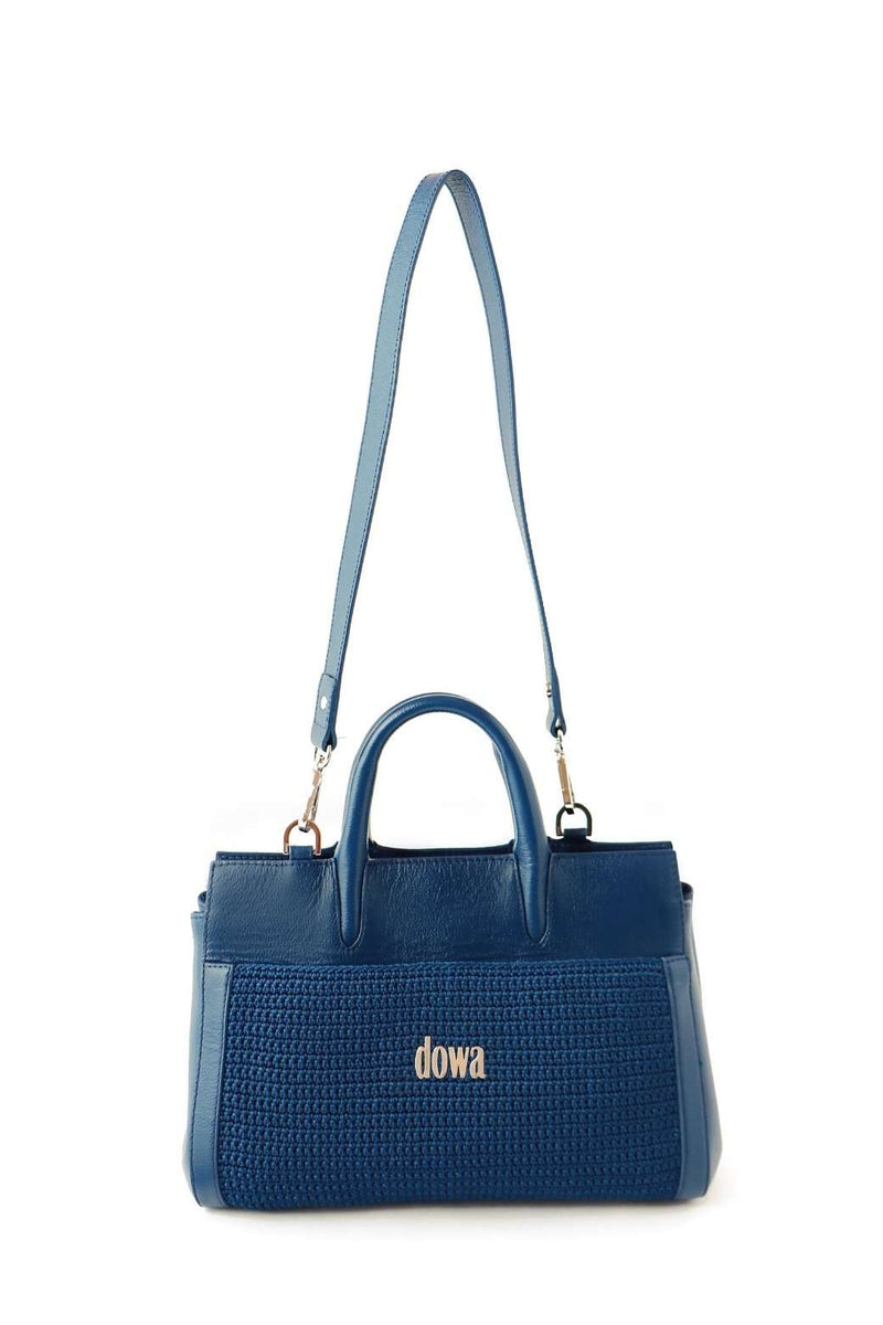 Twilight Blue hand-crafted ladies handbag, with a detachable shoulder strap and dual top tubular handles. Crochet style on the exterior and a Dowa metal silver logo attached on the centre. Discrete external zip at the top.