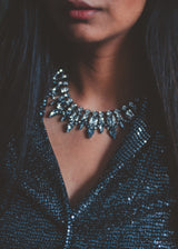 close up view of model, wearing a statement crystal necklace.