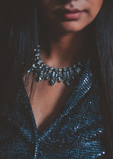 close up view of model, wearing a statement crystal necklace in a bling black jacket