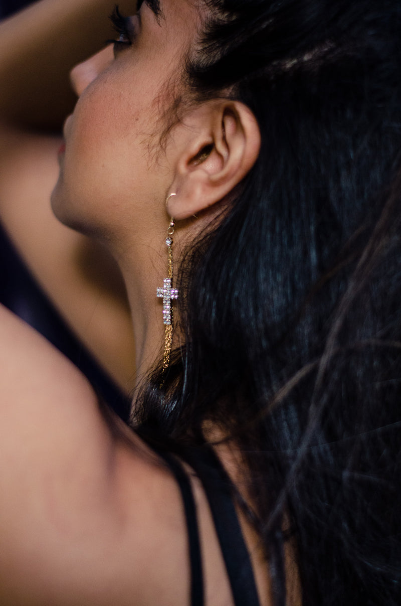 Back side view of model wearing crystal cross dangling earring.