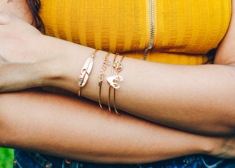 Close up picture of four gold coloured bangles, each with an element: snowflake, deer, love and leaf; on model's arm.
