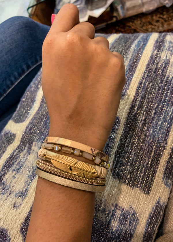 Front view of model wearing a five-layer cream and gold bracelet with different elements like leaf, beads and leather.