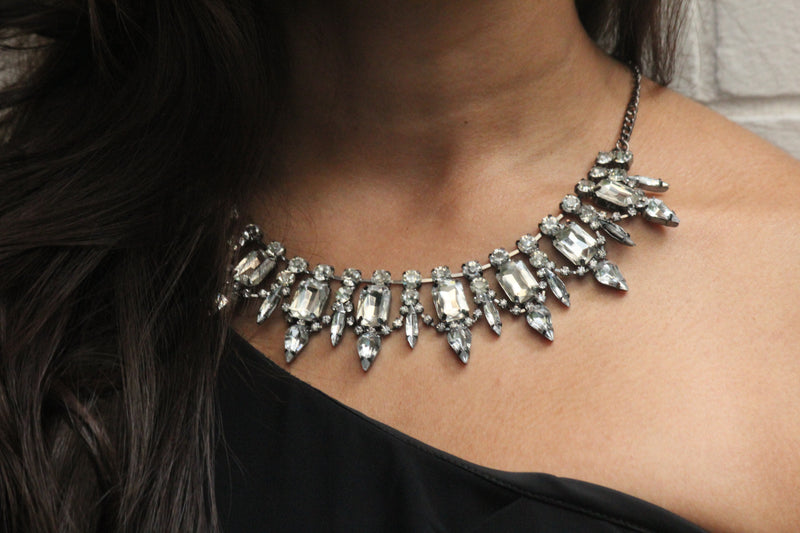 close up view of model, wearing a statement crystal necklace in a black one shoulder dress.