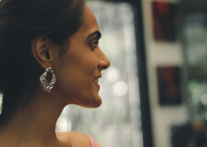 Close-up view of model wearing crushed foil type silver short earring.