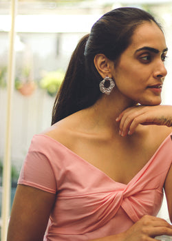 Side view of model wearing crushed foil type silver short earring, in a pink top.