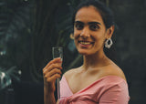 Front view of model wearing crushed foil type silver short earring, in a pink top holding a champagne glass.