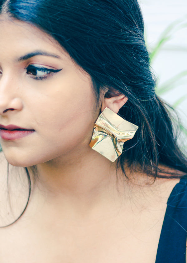 Side profile of model wearing gold crumbled short earring.