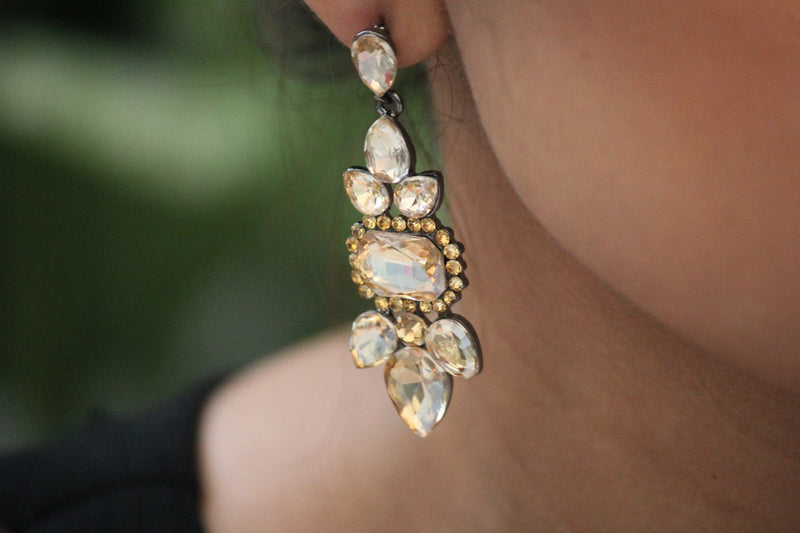 Close up of the champagne coloured rhinestone and crystal earrings on the ear of the model.