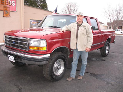 Gerry standing with his new purchase of a crew cab short bed from Handpicked Trucks.