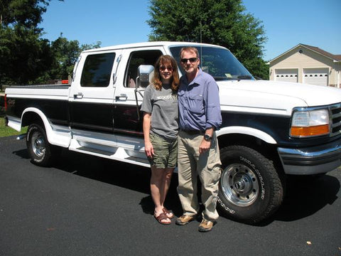 Richard and Sara T. standing happily with their new to them OBS Ford crew cab short bed from Handpicked Trucks.