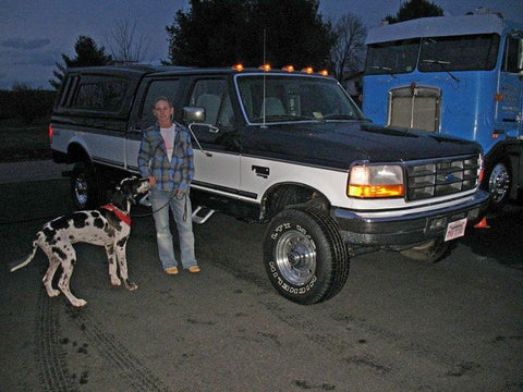 Victoria S. and Otto standing with her new OBS Ford purchased at Handpicked Trucks.