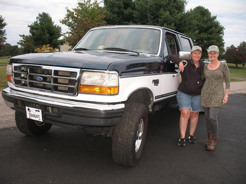Mary and Tammerie standing with their new OBS Ford truck from Handpicked Trucks.