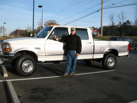 Jay Cutchin standing with his new crew cab short bed 97 F250 after taking delivery of it in North Carolina.