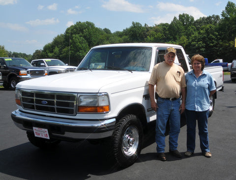 Ronnie and Brenda A. standing with their beautiful OBS they purchased from Handpicked Trucks.