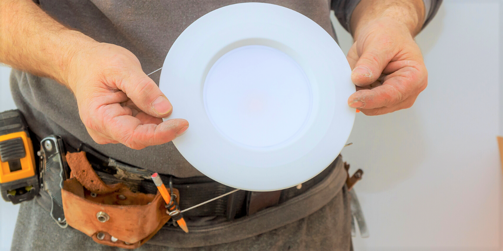 Electrician holding white recessed lighting bulb