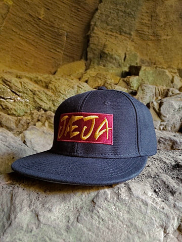 Jaeja snapback hat on rocks front view