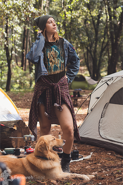 Woman camping with dog wearing unisex black Midnight Encounter sasquatch unicorn shirt by Fernweh Gear