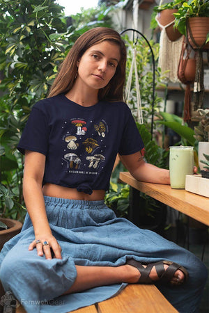 front view woman sitting with plants wearing Mushrooms of Oregon women's shirt (navy) - Fernweh Gear