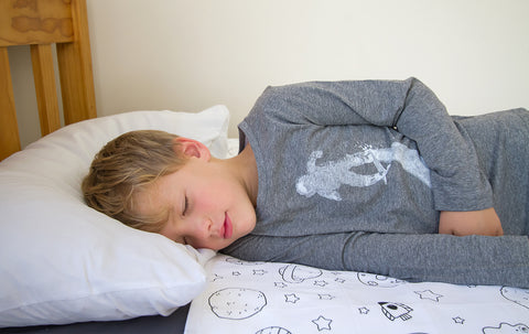 Boy asleep on a Brolly Sheet cotton, waterproof bed pad.