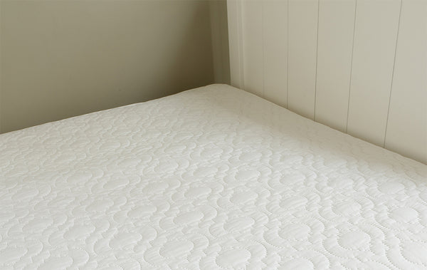 A quilted mattress protector on a bed