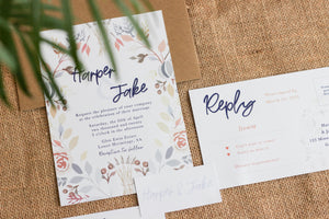 Floral invitation, tag and RSVP card laid out with an envelope.